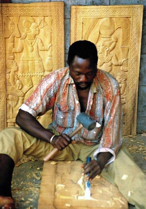 Nigerian master carver Shegun Adelodun carving wooden shutters.