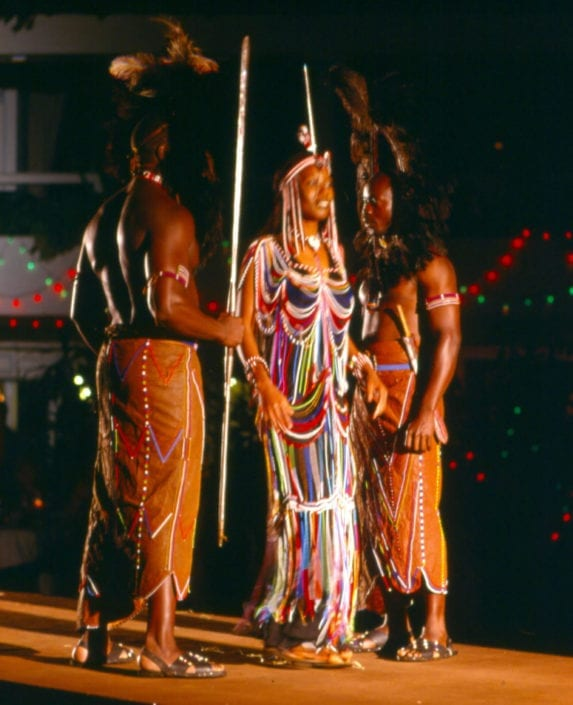African Heritage model Epiphany in Maasai beaded costume with Maasai warriors.