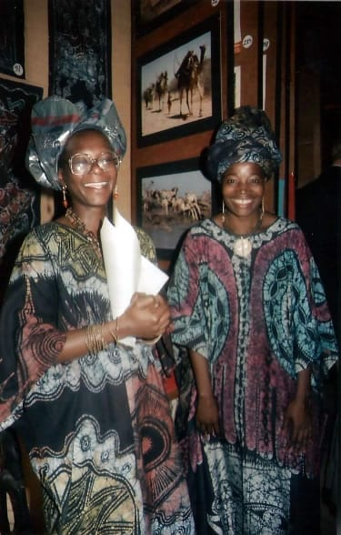 Nigerian batik artist Nike Seven Seven at one of her many exhibitions at African Heritage being interviewed by Kenyan woman wearing one of her batik gowns